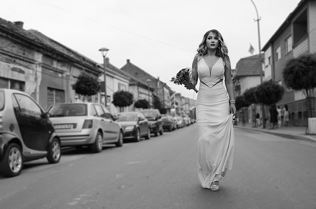 Devojka u beloj haljini šeta ulicom i drži buket cveća